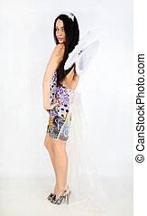 Young beautiful girl with white wings wearing dress