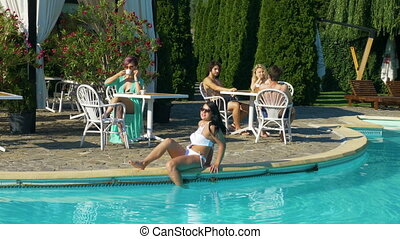 Young beautiful group of people spending time at the pool in a summer day