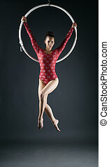 Young beautiful gymnast performs with hoop