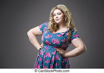 Young beautiful happy blonde plus size model in dres, xxl woman portrait on gray studio background