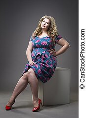Young beautiful happy blonde plus size model in dress and shoes, xxl woman on gray studio background