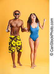 Young beautiful happy cheerful couple in beachwear holding hands isolated on the orange background
