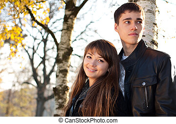 Young beautiful happy smiling couple in love against the background of beauti sunny autumn nature