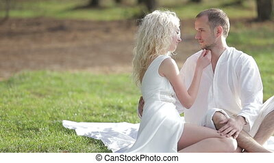 Young beautiful  happy couple in the woods. She softly strokes his face