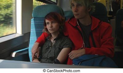 Young beautiful happy hipster couple riding by the train and looking to the window. Summer vacation.