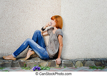 Young beautiful happy redhead teenage woman model girl sitting against wall and looking up excited on copy space