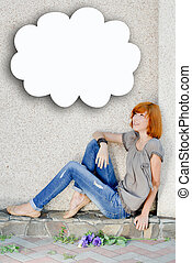 Young beautiful happy redhead teenage woman model girl sitting against wall and looking up on copy space