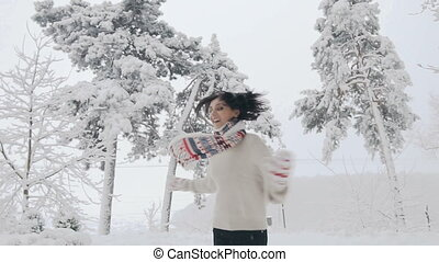 Young beautiful happy, smiling girl on the street catching snowflakes and joyfully jumping around and looking into the camera. Snowfall Christmas, New Year