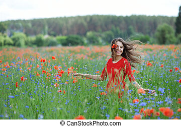 Young beautiful happy woman have a fun in spring poppy field. Concept freedom and happiness summer