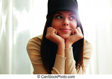 Young beautiful happy woman in hat looking away