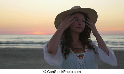 Young beautiful happy woman posing on the beach at sunset