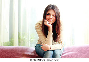 Young beautiful happy woman sitting on the sofa at home