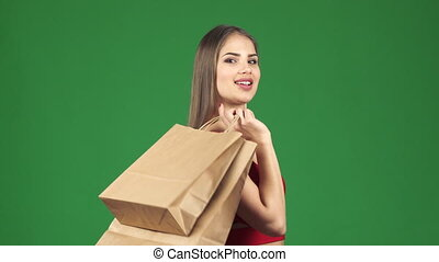 Young beautiful happy woman smiling holding shopping bags on chromakey
