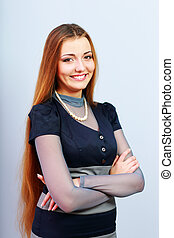 Young beautiful happy woman with arms folded on gray background