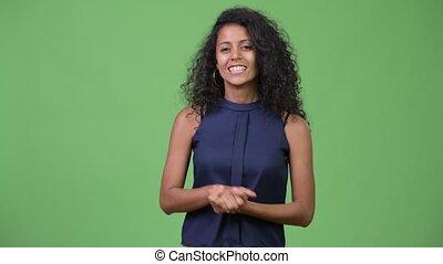 Young beautiful Hispanic businesswoman presenting something