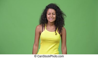 Young beautiful Hispanic woman looking excited