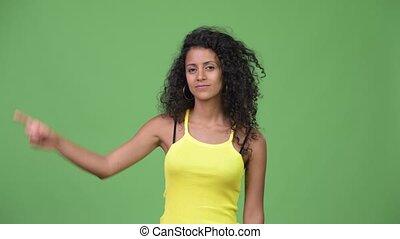 Young beautiful Hispanic woman pointing up