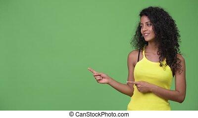 Young beautiful Hispanic woman showing something