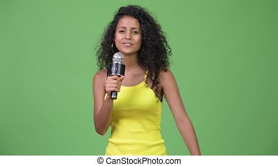 Young beautiful Hispanic woman singing
