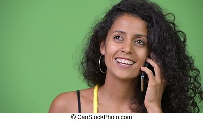 Young beautiful Hispanic woman talking on the phone