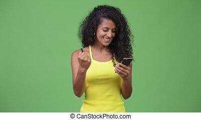 Young beautiful Hispanic woman using phone and getting good...