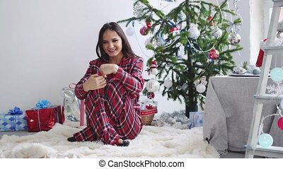 Young beautiful joyful brunette in pajamas sits on a rug near a Christmas fir-tree in anticipation of the New Year. slow motion. 3840x2160