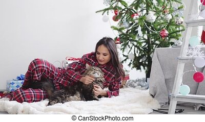 Young beautiful joyful woman lying beside Christmas fir-tree on a rug playing with Maine Coon cat. slow motion. 3840x2160