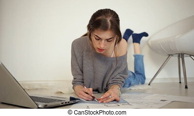 Young beautiful lady lying on the floor and working with her laptop at home.