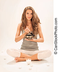 Young beautiful lady relaxing with nepal singing bowl and ...