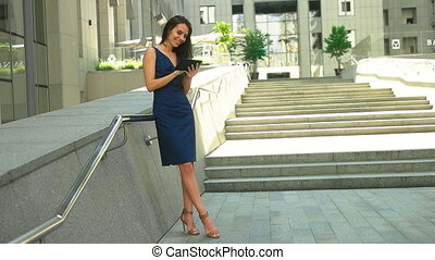 Young beautiful lady using tablet while staying indoors near big business center in a lunch time.