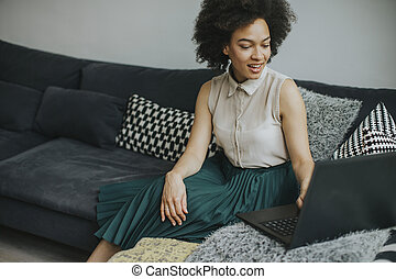 Young beautiful lady with curly hair work on the notebook while sit down on the couch at home