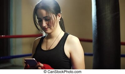 Young beautiful latino woman girl dials text on a smartphone gadget, is playing, smiling. Against the background of a punching bag