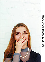 Young beautiful laughing woman looking up at copyspace isolated on a white background