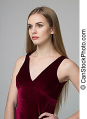 Young beautiful long-haired girl poses in red dress