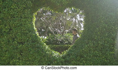 Young beautiful man and woman hug each other in the garden in Vietnam. Happy loving couple at the honeymoon are kissing, looking into eyes to each other and enjoying romantic moment. Love story.