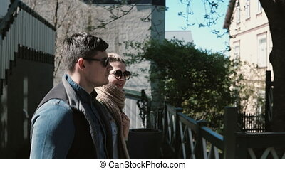 Young beautiful man and woman walking in sunny urban city. Stylish couple on a romantic date together.