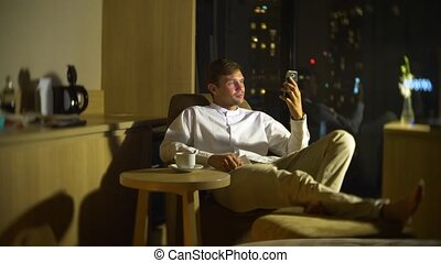 Young, beautiful man using a smartphone, on a chair in a room with a panoramic window overlooking the skyscrapers at night. blur the background.