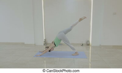 Young beautiful model woman exercising various yoga poses on a mat and stretching her muscles