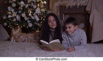 Mom reads a book to her son and kisses him lying on the floor near the Christmas tree on Christmas day