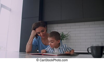 Young beautiful mother and son sitting at a table in a...