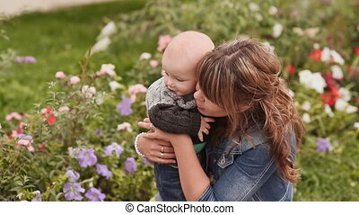 Young beautiful mother is sitting with her young son on a floral lawn.