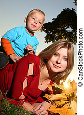 Young beautiful mother lying on green grass with her son and holding bouquet of yellow autumn leaves.
