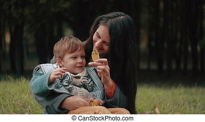 young beautiful mother playing with her cute little son, who is sitting on her lap in the autumn park