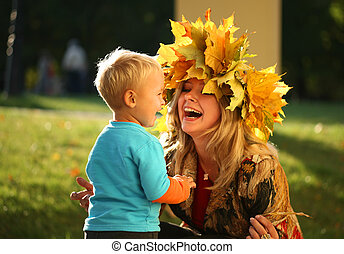 Young beautiful mother playing with her little son in an autumn park.
