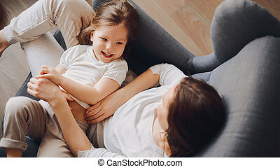 mother with a 3-year-old daughter sit in a gray armchair, hug and laugh