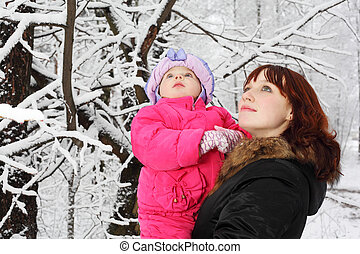 Young beautiful mother with little daughter look up in woods in snow at winter