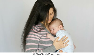 Young beautiful mother with long dark hair is holding a newborn infant baby of two months on white background in studio