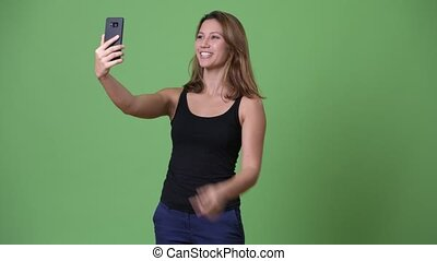 Young beautiful multi-ethnic woman against green background...