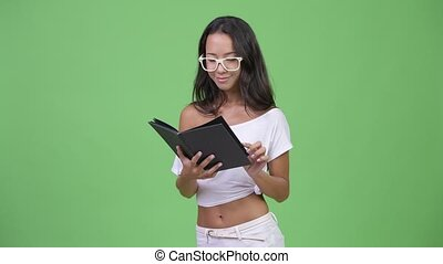 Young beautiful multi-ethnic woman reading book with eyeglasses