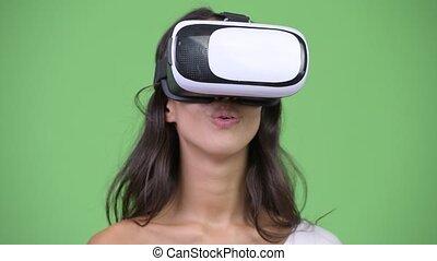 Young beautiful multi-ethnic woman using virtual reality headset